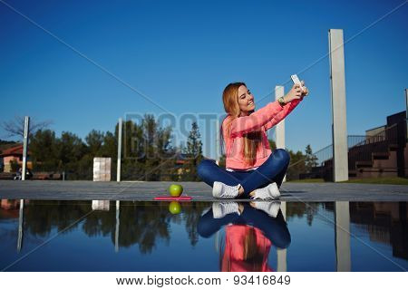 Young attractive girl sitting near the fountain on a sunny day and makes self on your mobile phone