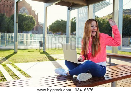 Young girl freelancer working on his laptop while sitting on a park bench and waving his friends
