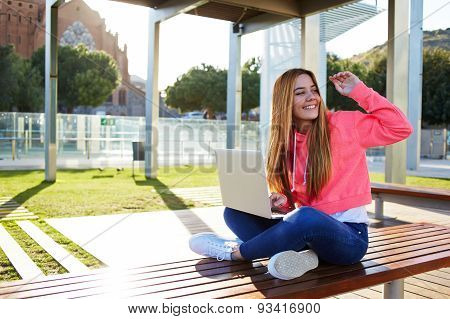 Charming girl sitting on a bench on a sunny day with an open white laptop and waving his friends