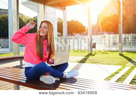 Student sitting on a bench on a sunny day holding a laptop on his knees and waved to someone