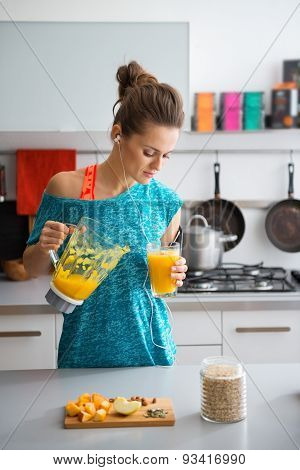 Woman In Workout Gear Pouring Smoothie In Kitchen