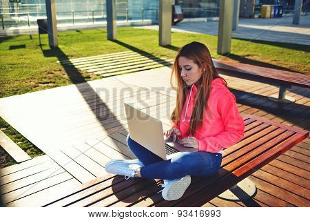 Portrait of a young student of prints text on laptop keyboard sitting on a bench at college