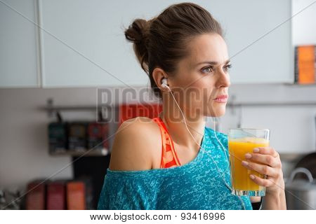 Closeup Of Woman In Profile Wearing Workout Gear Holding Juice