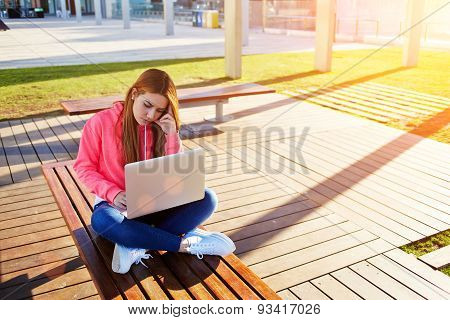 Young beautiful blonde sitting on a bench with a laptop and viewing information on the Internet