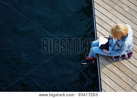Freelancer girl sitting on a wooden pier holding a tablet and prints  message using the touch screen