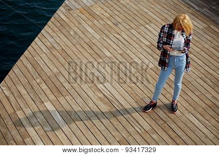 Young girl tourist standing on the wooden pier and viewing photos on the touch screen tablet
