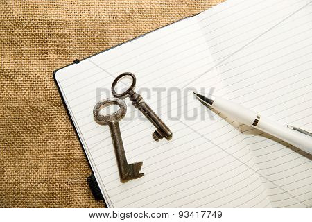 Opened Notebook, Keys And Pen On The Old Tissue
