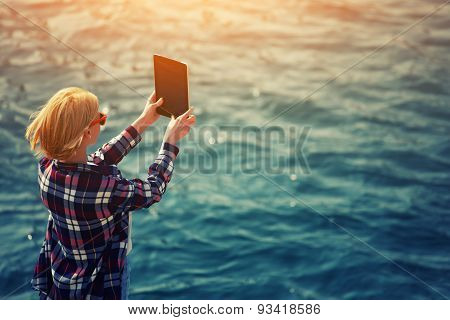 Back view of a woman taking picture with a digital tablet camera standing against sea.