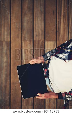 Top view shot of girl holds the tablet with a touch screen on a black background empty wooden floor