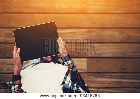 Portrait of a young attractive girl standing with a touch tablet on the wooden floor in a sunny day