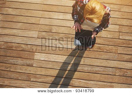 Young attractive girl stands with a touch tablet on the wooden floor in a sunny day