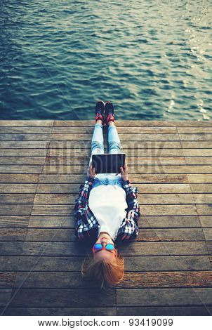 Active young stylish girl resting after a walk on a wooden pier and makes the photo on tablet