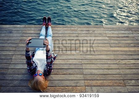 Young teen woman relaxing upon a wooden jetty while taking self portrait holding up tablet