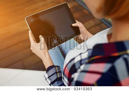 Young woman's hands hold black tablet with blank empty screen