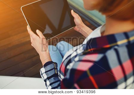 Hands of a young woman is holding a touch tablet with blank black screen