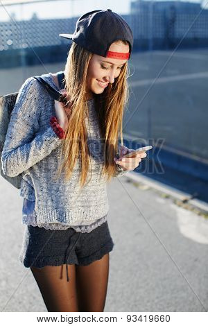 Stylish young girl standing on the street and smiling looking at pictures in the phone