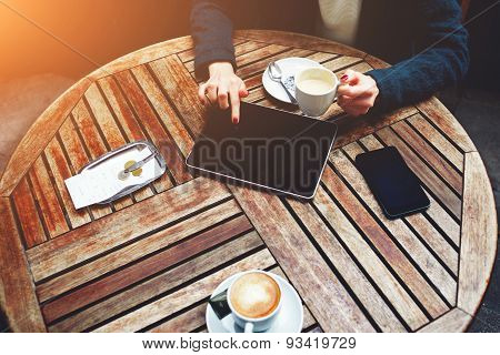 Elegant woman sitting and using touch screen tablet while drink cappuccino bill check and phone