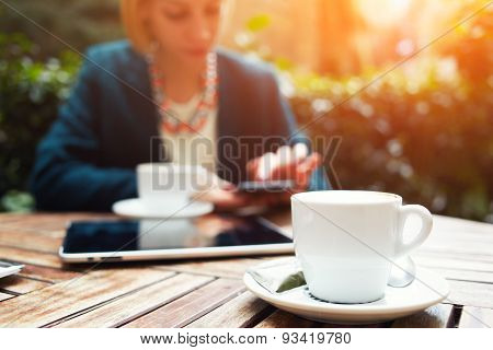Business ladies sitting at the table drinking coffee and working on the mobile phone and tablet
