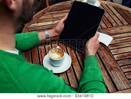 Rear view of male freelancer holding digital tablet with empty screen man sitting at the table