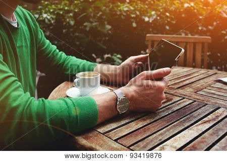 Young freelancer sitting on the terrace with cup of coffee and touch screen tablet