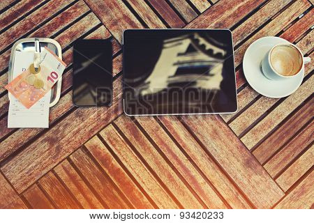 Mobile phone,tablet,bill check with money and coffee cup standing on a wooden table