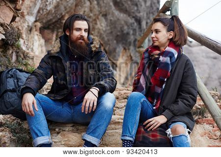 Portrait of a young couple active travelers sitting on a rock resting from his long journey