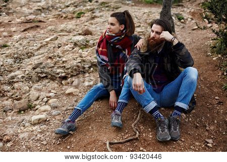 Young active couple of tourists sitting on rocks resting after his long walk in the mountains