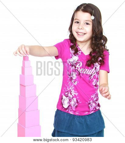 The girl is too young to attend school pink builds a pyramid in