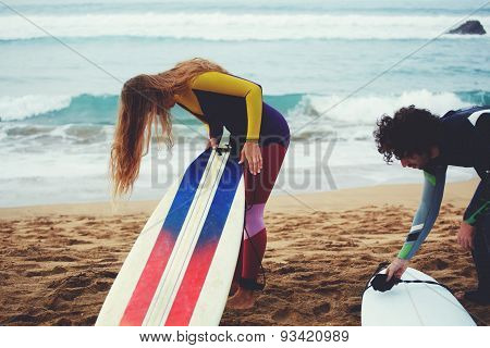 Portrait of two young active people dressed in wetsuit preparing to surf in the warm summer evening