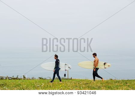 Two young friends surfers walk on the beach holding a surfboard