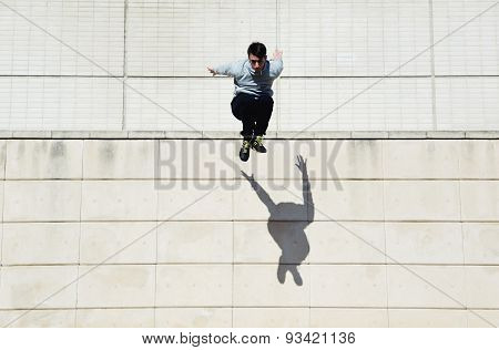 Male parkour free runner jumping forward from high rooftop over cement building background