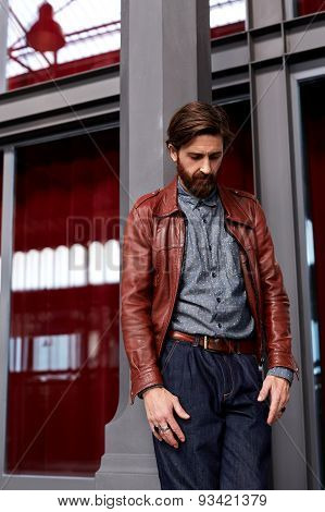 Posing indoors fashionable mature man with beard on beautiful glassy background
