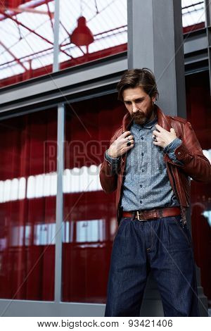 Man with beard posing indoors adjusting his leather jacket against glassy reflective wall