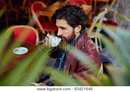 Side view through plant leaves pensive hipster man holding cup of tea sitting on the coffee shop