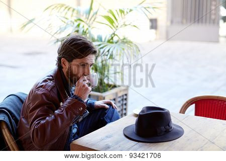 Portrait of fashionable man holding cup of tea next to his mouth while sitting on the terrace
