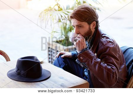 Portrait of handsome man who drinking tea or coffee while sitting on the terrace coffe shop .