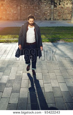 Portrait of a stylish young man with black hair and beard walking down the street on a sunny day.