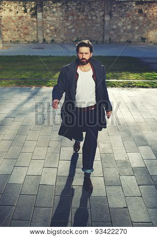 Portrait of elegant fashionable adult man dressed in coat walking on the street at sunny evening