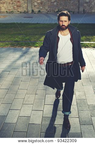 Elegant fashionable stylish hipster man walking on the street at sunny evening filter
