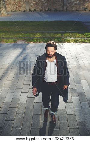 Young stylish hipster man walking on the street at sunny evening filter