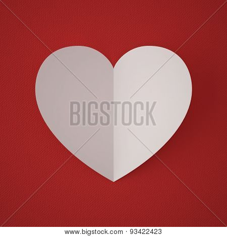 Valentine's Day. White paper heart on a red background fabric.