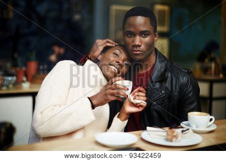 Portrait of young couple in love having fun drinking coffee in cafe romantic dark skinned couple.