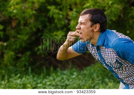 Man on the street nausea vomiting on a green  background  leaves