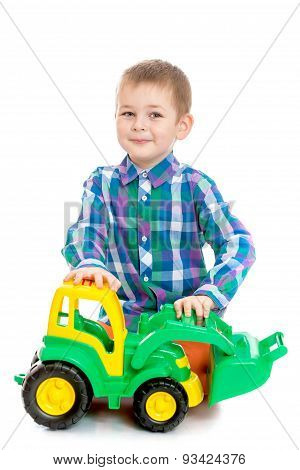Fair-haired little boy playing with a toy tractor sitting on the