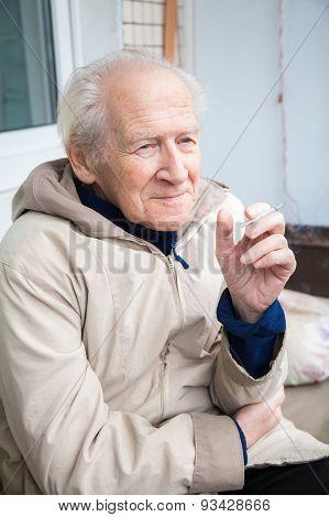 Old Man Enjoying A Cigarette