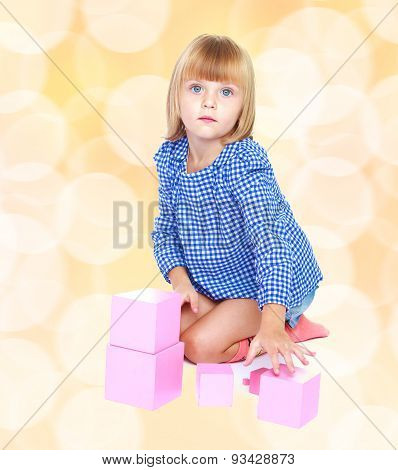 Adorable little blonde girl is sitting on the floor and playing
