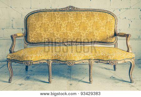 Vintage luxury yellow sofa with white brick wall background