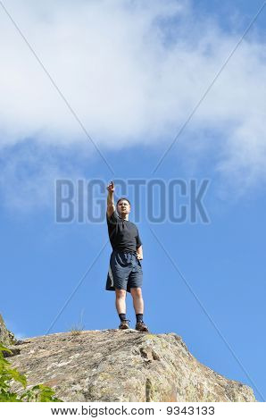 A young man stands on a cliff top and raised his hands