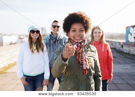 people, friendship and international concept - happy african american young woman or teenage girl pointing finger to you in front of her friends on city street