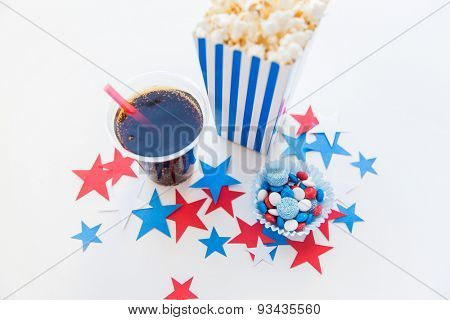 american independence day, celebration, patriotism and holidays concept - close up of coca cola cup, popcorn and candies with stars confetti decoration at 4th july party